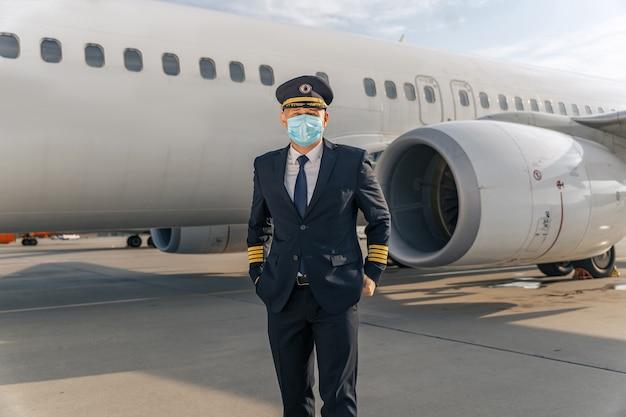 항공기 근처에 서 있는 마스크를 쓴 항공사 조종사