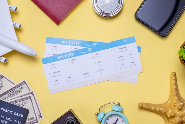 Airline tickets and accessories for travel and vacations on a yellow background