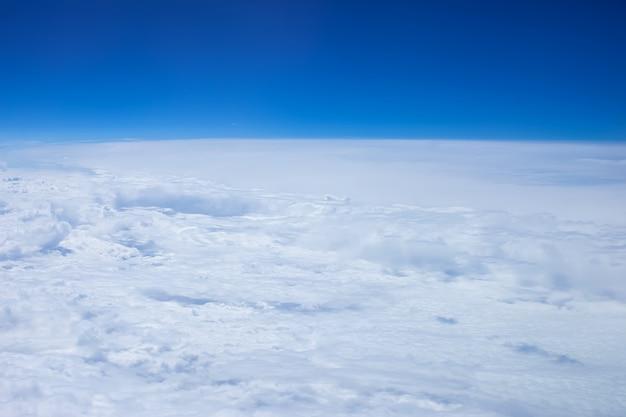 大きな白い厚いふわふわの雲の飛行機の窓側の座席ビュー