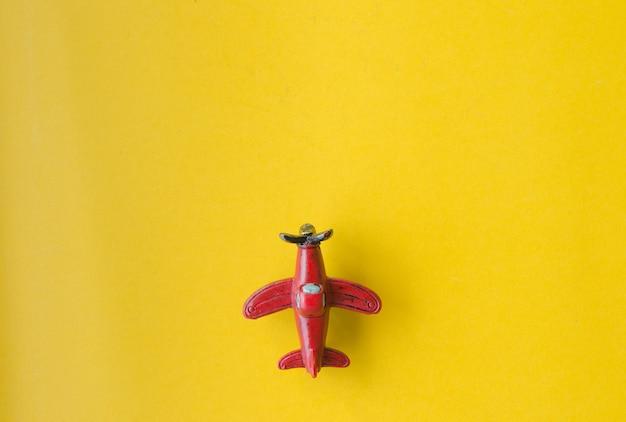 黄色の紙の背景に飛行機のおもちゃ