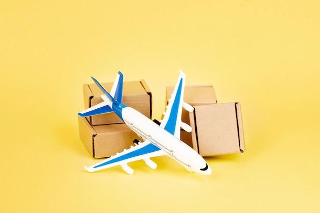 비행기와 골판지 상자 더미입니다. 항공 화물 및 소포, 항공우편의 개념입니다. 상품 및 제품의 빠른 배송. 화물 항공기. 물류, 접근하기 어려운 곳으로 연결. 배너, 복사 공간