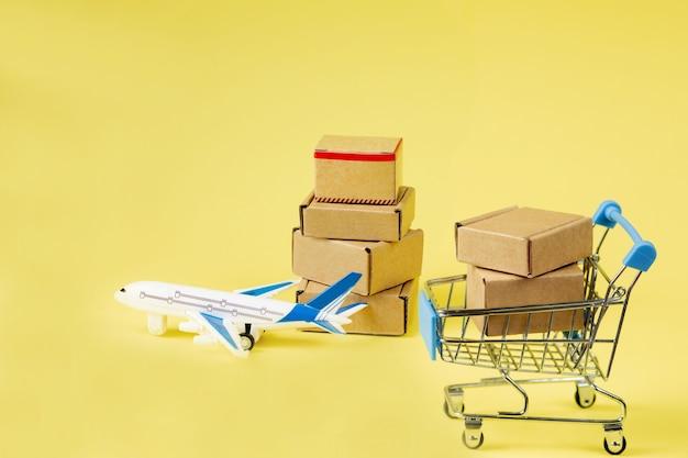 비행기와 골 판지 상자 스택입니다. 항공화물 및 소포, 항공 우편의 개념. 상품 및 제품의 빠른 배송. 화물 항공기. 물류, 도달하기 어려운 장소와의 연결. 배너, 복사 공간