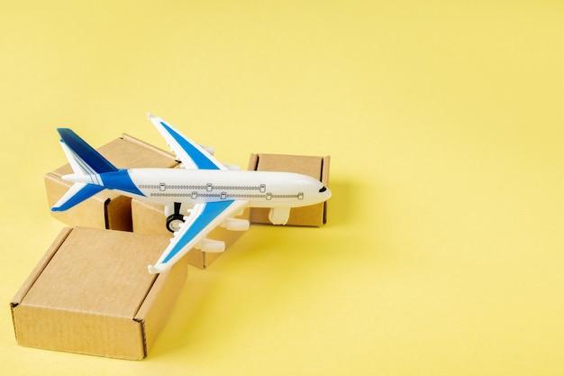 비행기와 골 판지 상자 스택입니다. 항공화물 및 소포, 항공 우편의 개념. 상품 및 제품의 빠른 배송. 화물 항공기. 물류, 접근하기 어려운 장소와의 연결. 배너, 복사 공간