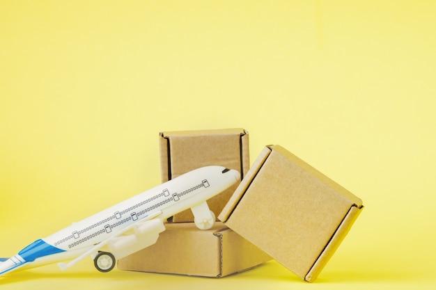 비행기와 골판지 상자 더미입니다. 항공 화물 및 소포, 항공우편의 개념입니다. 상품 및 제품의 빠른 배송. 화물 항공기. 물류, 접근하기 어려운 곳으로 연결.