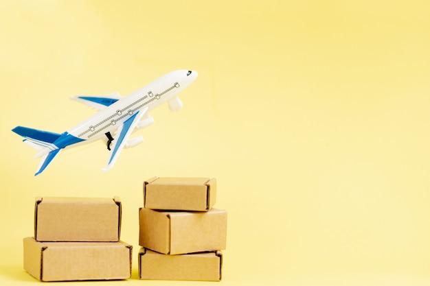 비행기와 골 판지 상자 스택입니다. 항공화물 및 소포, 항공 우편의 개념. 상품 및 제품의 빠른 배송.
