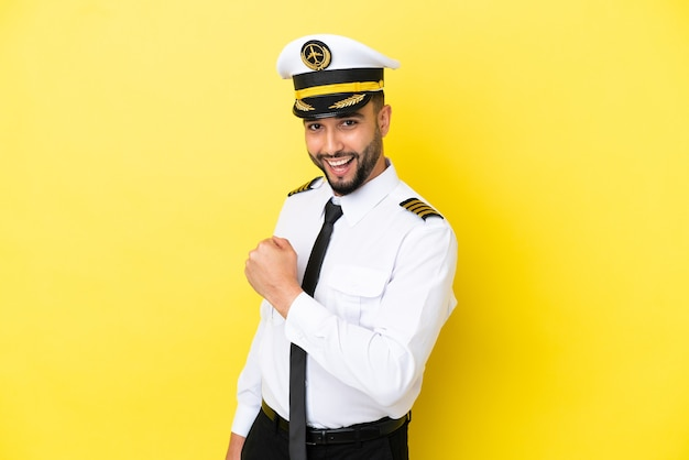 勝利を祝う黄色の背景に分離された飛行機のアラブパイロット男