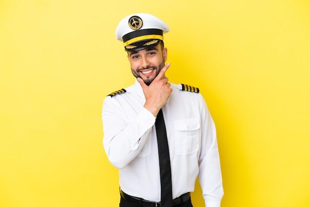 幸せと笑顔の黄色の背景に分離された飛行機アラブパイロット男