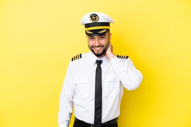 笑って黄色の背景に分離された飛行機のアラブパイロット男
