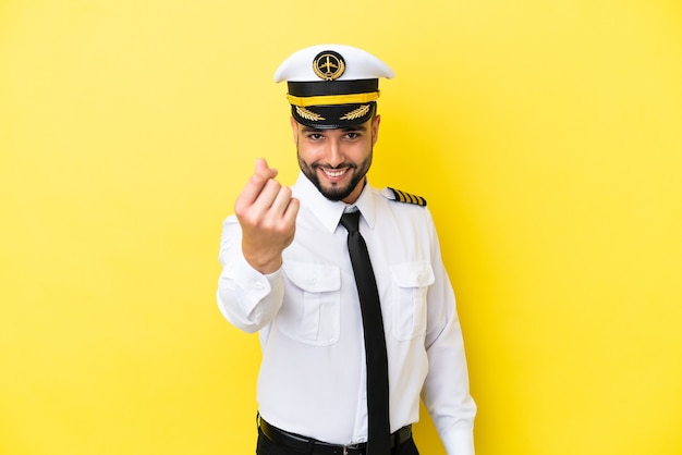 Человек-пилот самолета арабского происхождения изолирован на желтом фоне, делая денежный жест
