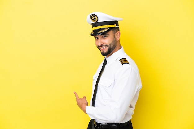 後ろ向きの黄色の背景に分離された飛行機のアラブパイロット男