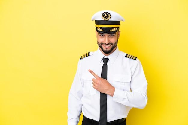 製品を提示する側を指している黄色の背景に分離された飛行機のアラブパイロット男