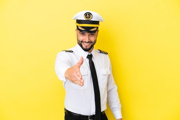 Человек-пилот самолета арабского происхождения изолирован на желтом фоне, пожимая руку для заключения хорошей сделки