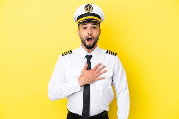 黄色の背景に分離された飛行機のアラブパイロットの男は、右を見ながら驚いてショックを受けました