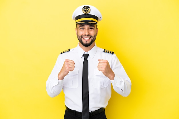 Airplane arab pilot man isolated on yellow background celebrating a victory in winner position