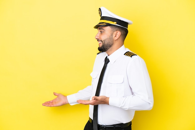 Airplane arab pilot man isolated on yellow background with surprise expression while looking side