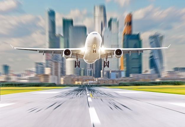 空港の飛行機は、街と高層ビルを背景に離陸します。