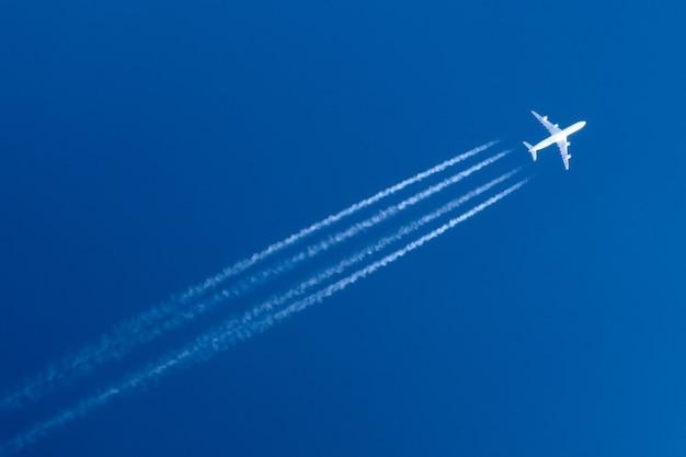 飛行機の大きな4つのエンジンの航空空港の飛行機雲。