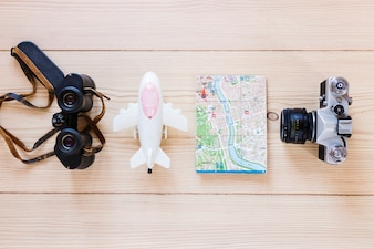 Airplane; binoculars; map and camera on wooden backdrop