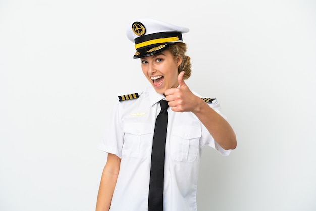 좋은 일이 일어났기 때문에 엄지손가락으로 흰색 배경에 고립 된 비행기 금발 여자 조종사