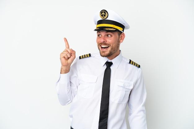 Бразильский пилот самолета изолирован на белом фоне, намереваясь реализовать решение, подняв палец вверх