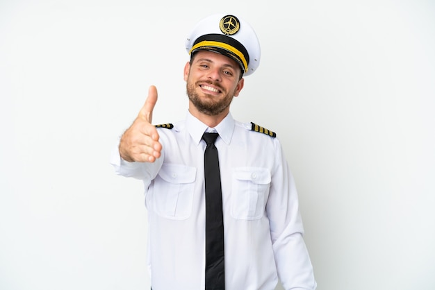 Airplane brazilian pilot isolated on white background shaking hands for closing a good deal