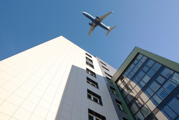 Airplane above building on blue sky background