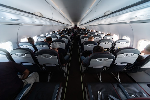 Airplane cabin seats with passengers. economy class of new cheapest low-cost airlines