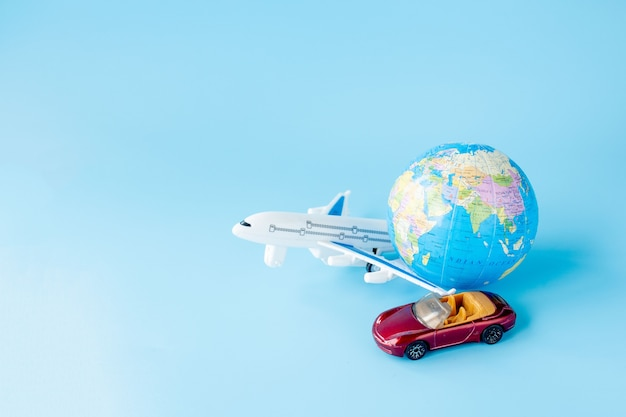 Airplane, car and globe on blue wall. summer or vacation concept. copy space.