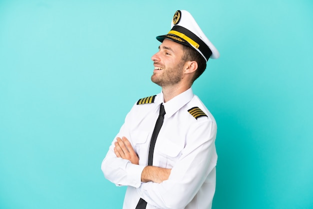 Airplane caucasian pilot isolated on blue background happy and smiling