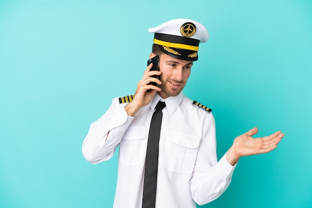 Airplane caucasian pilot isolated on blue background keeping a conversation with the mobile phone with someone