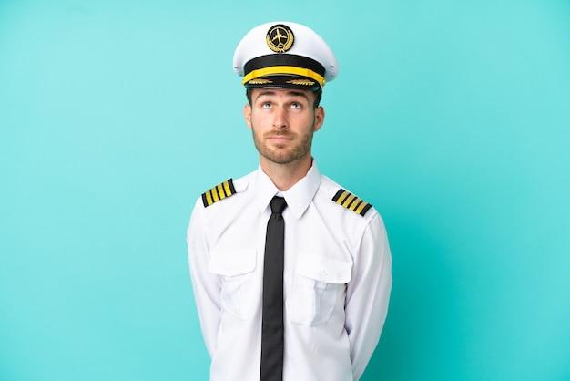 青い背景に分離され、見上げる飛行機の白人パイロット