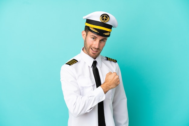勝利を祝う青い背景に分離された飛行機の白人パイロット
