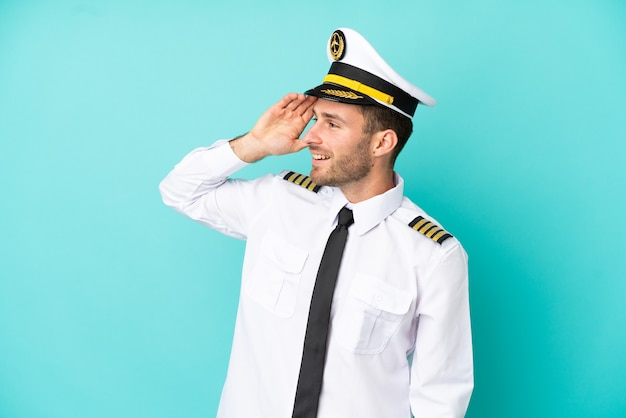 青い背景に分離された飛行機の白人パイロットは何かを実現し、解決策を意図しています