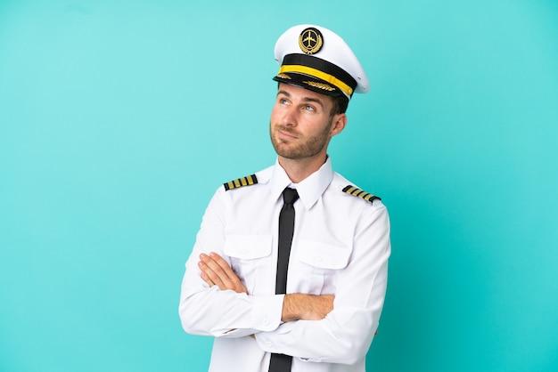 笑顔で見上げる青い背景に分離された飛行機の白人パイロット