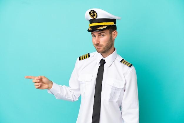 横に指を指している青い背景に分離された飛行機の白人パイロット