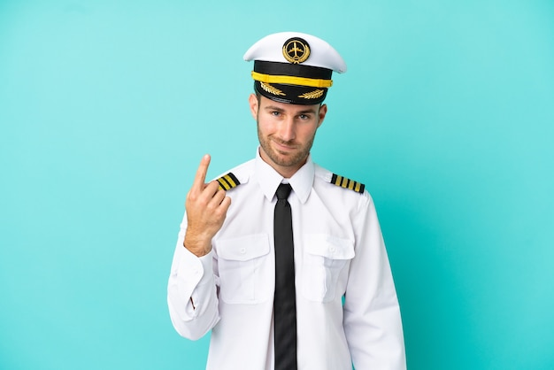 人差し指で指している青い背景に分離された飛行機の白人パイロット素晴らしいアイデア