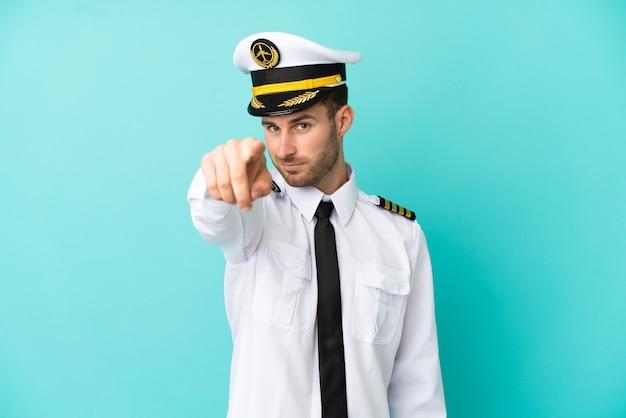 青い背景に分離された飛行機の白人パイロットは自信を持ってあなたに指を指しています