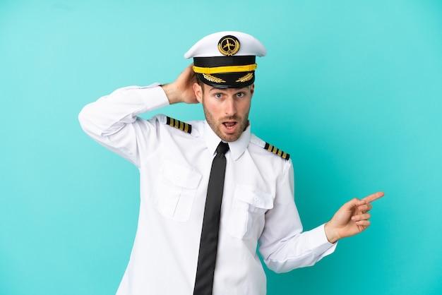 青い背景に分離された飛行機の白人パイロットは驚いて、人差し指を横に向けています