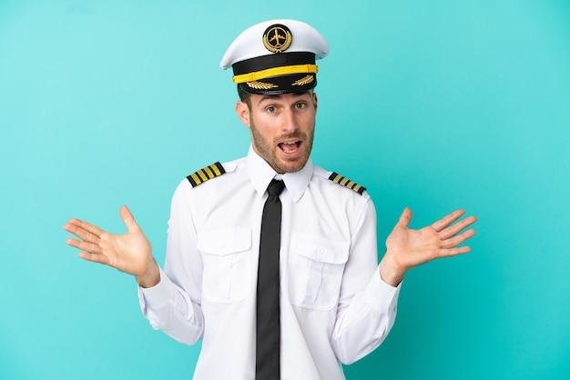 ショックを受けた顔の表情で青い背景に分離された飛行機の白人パイロット