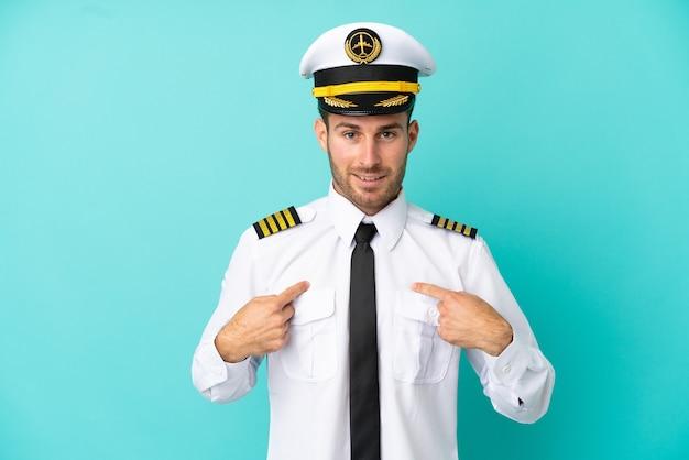 驚きの表情で青い背景に分離された飛行機の白人パイロット