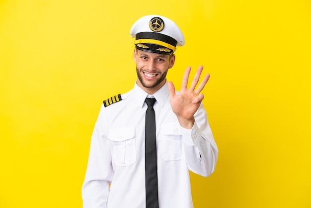 Кавказский пилот самолета изолирован на желтом фоне счастлив и считает четыре пальцами