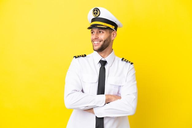 幸せと笑顔の黄色の背景に分離された飛行機の白人パイロット