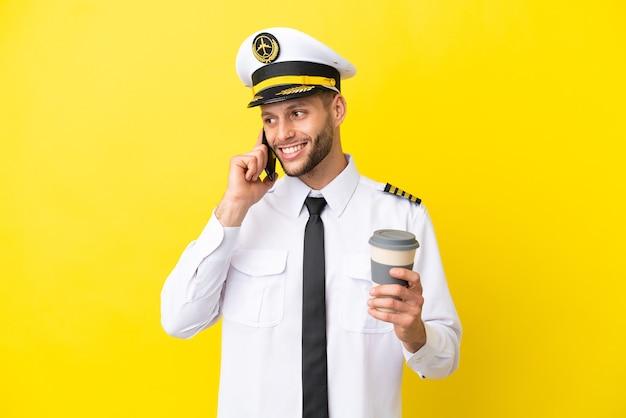 Пилот самолета кавказской изолирован на желтом фоне, держа кофе на вынос и мобильный