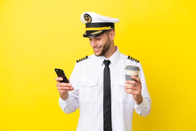 持ち帰り用のコーヒーと携帯電話を保持している黄色の背景に分離された飛行機の白人パイロット