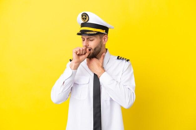 黄色の背景に分離された飛行機の白人パイロットは咳と気分が悪いに苦しんでいます