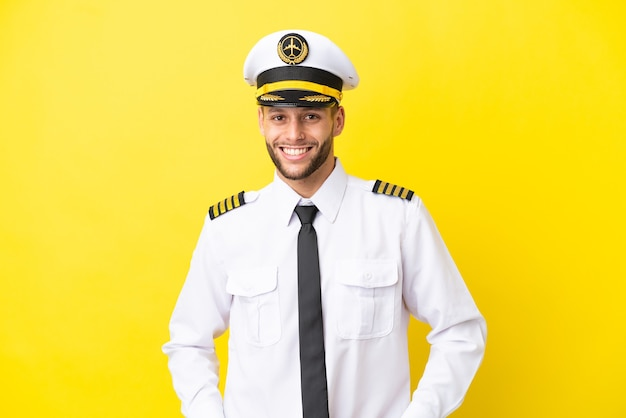 笑って黄色の背景に分離された飛行機の白人パイロット