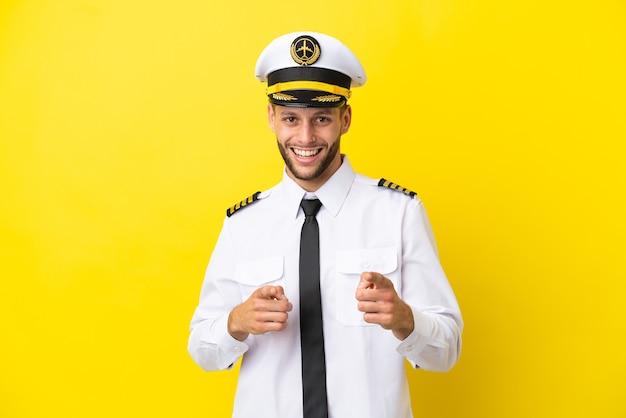 正面を指して笑顔で黄色の背景に分離された飛行機の白人パイロット