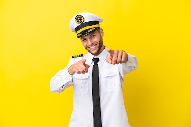 黄色の背景に分離された飛行機の白人パイロットは、笑顔であなたに指を指しています