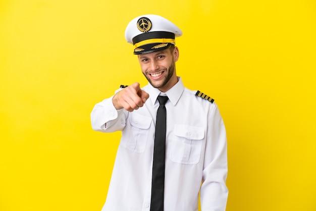 黄色の背景に分離された飛行機の白人パイロットは自信を持ってあなたに指を指しています