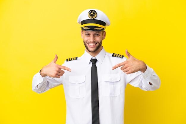 誇りと自己満足の黄色の背景に分離された飛行機の白人パイロット